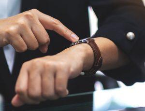 Dringlichkeitsvergabe: Frau schaut auf Armbanduhr